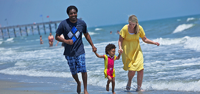 Family running on the beach in Myrtle Beach, SC